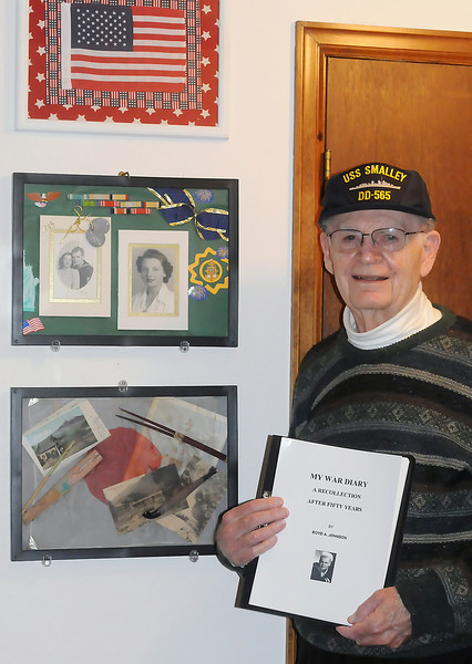 "Loveland resident Boyd Johnson holds a copy of his book, ""My War Diary,"" as he poses in his home Friday in front of some memorabilia from his military service during World War II."