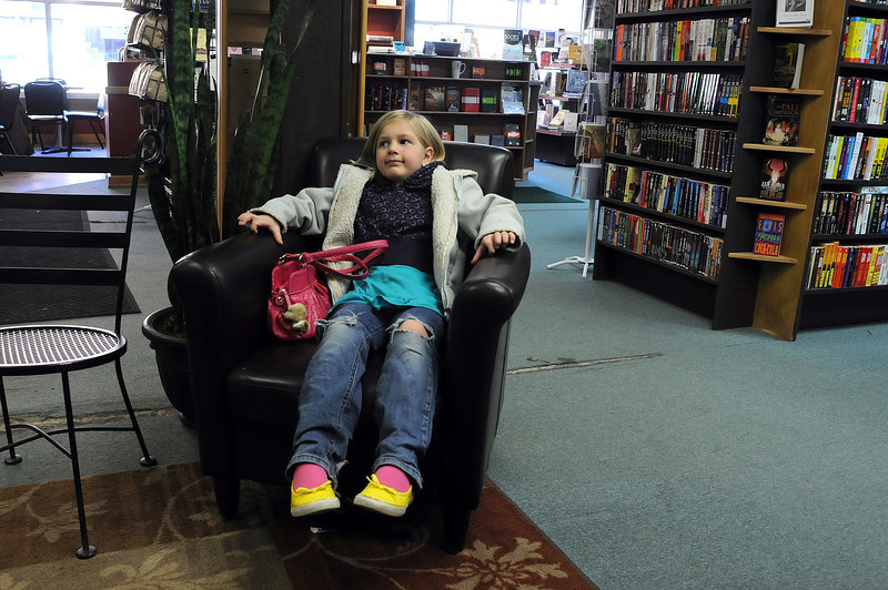 Ella Montagu, 6, waits for her parents at Anthology Book Company on Sunday in downtown Loveland. Montagu and her family often come to downtown Loveland on Sundays to visit with a family friend.