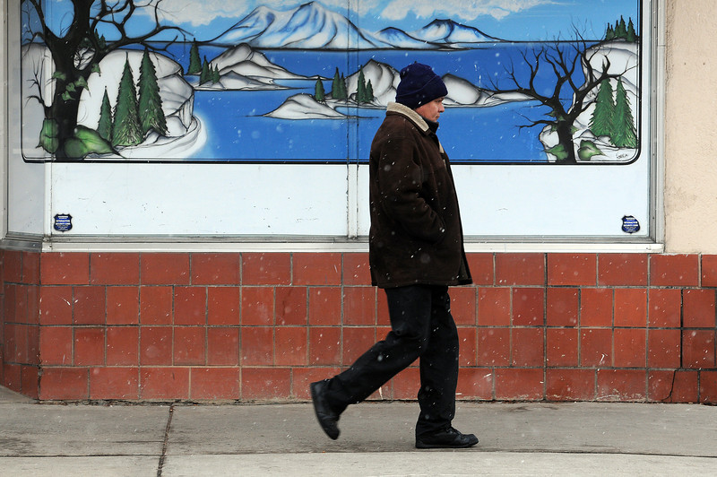 Sergio Feliciano of Loveland walks down Cleveland Avenue amidst snow flurries on his way to work on Sunday. The flurries didn't last that long or collect and today's forecast calls for mostly sunny skies with highs from 35 to 40 degrees.