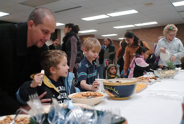 Loveland residents, from left, Oren Yakovee, Josiah Powers, 4, and Airiel Siegel, 7, get some snacks in the commons area at Thompson Valley High School on Monday night as part of the Martin Luther King Day celebration's social hour.