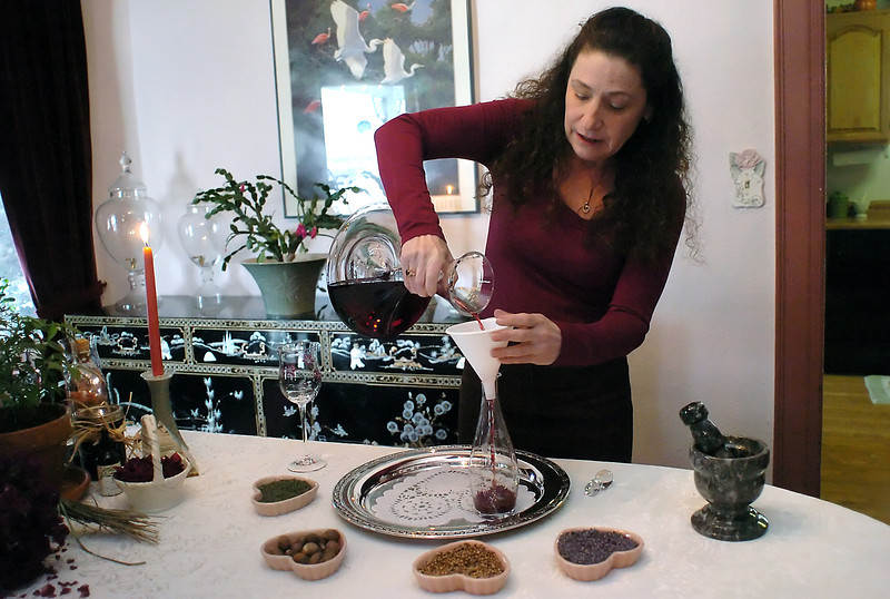 "Loveland resident Donna Wild pours a love potion she made into a decanter after mixing the various ingredients Tuesday during a demonstration in her home. Wild is a self-taught herbalist and nutritionist and will teach a ""love potions and sensual scents"" class from 9 a.m. to noon on Saturday, Feb. 6 at the Chilson Recreation Center, 700 E. Fourth St."