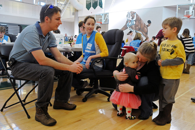 Heather Hafer of Loveland comforts her daughter Sally after the one year old received her H1N1 booster shot as her father Richard Hafer, left, and vaccinator Savannah Bennett, center, talks  the Hafer's son Remy, 4, into the flu mist option. Sunday's clinic at Fossil Ridge High School marked Larimer County's final H1N1 clinic.