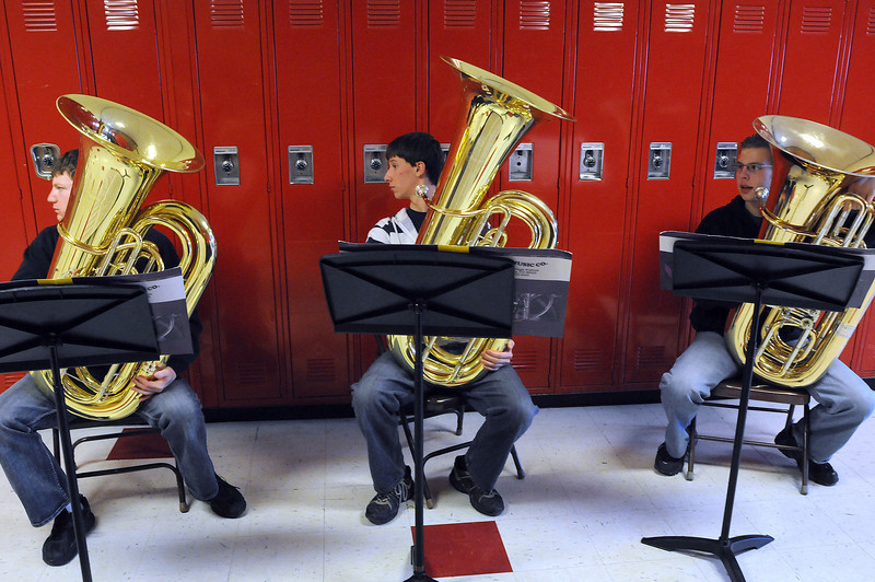 Tuba players Zach Henderson, 17, left, Ben Tripam, 16, center, and Justin Tebbe, 15, work on a section of music that features tuba on Friday during a class at Loveland High School. The school's wind symphony will attend the Western International Band Clinic in Seattle, Wash, next year.
