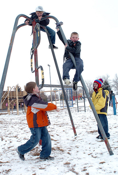 Sarah Milner Elementary School students Logan Kreiling, 9, left, and Chance Cross, 10, right, look up at Gage Ashlock, 10, top, and Brian Abbott-Clark, 8, while playing together Thursday afternoon during recess on the school's playground.