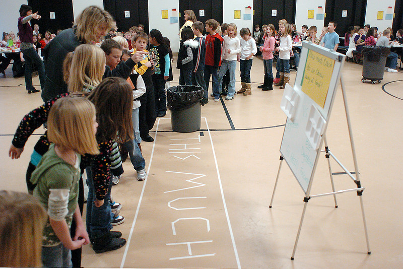 Stansberry Elementary School students look at a sign in the lunchroom which has the old Styrofoam and new biodegradable lunch trays and also an area marked out on the floor representing how much trash the school generates over 3-4 days from their lunch period.