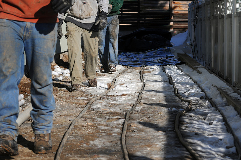 Bryon Holloway, foreground, Larry Volk, center, and Pat Testa lay tarps over heated tubing to thaw the ground so concrete can be poured at the new Sherwin-Williams paint store at 2033 West Eisenhower on Thursday.