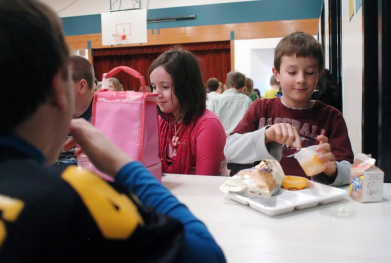 Stansberry Elementary School students eat lunch together in the school's cafeteria. At left is Jeremy Shomers, 9, and back from left are Colton Harris, 10, Dusty Berglund, 10, and Vance Zscheile, 9, whose lunch was served using a biodegradable tray that's new to the school.