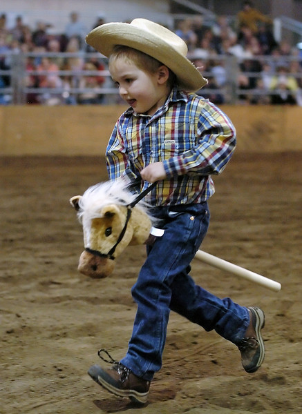 Three-year-old Eli Rexford of Greeley sprints around the Ranch-Way Feeds Arena atop his horse named Sugar while competing in the stick-horse race Saturday during the Big Thunder Draft Horse Show.