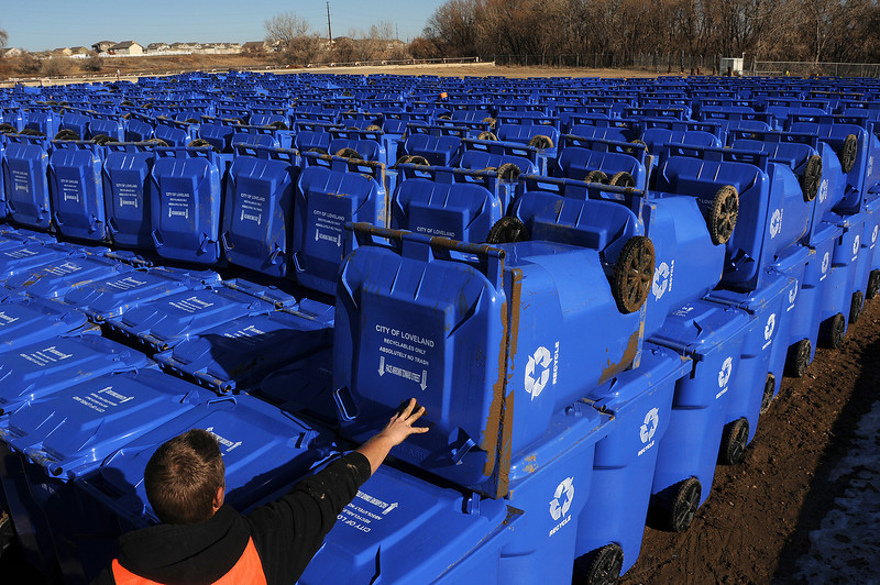 Nate Holstege of Loveland piles a recycling cart atop thousands of others on Nov. 29 at near the Loveland Water Treatment Plant as he and other members of the Larimer County Sheriff's workender crew assemble the carts for the upcoming single-stream program in which Lovelanders can mingle theier plastics, paper and glass recyclables.