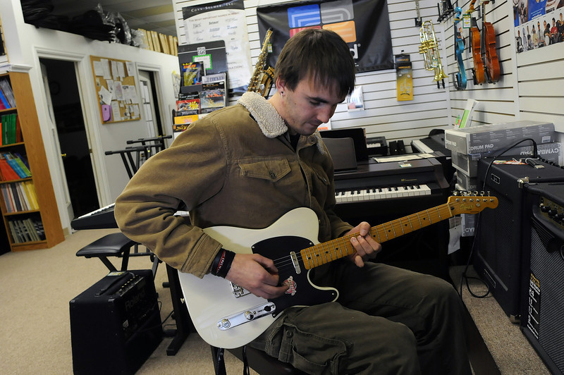 Ben Krug of Loveland tickles the frets of a Fender Squire Telecaster on Sunday in downtown Loveland.