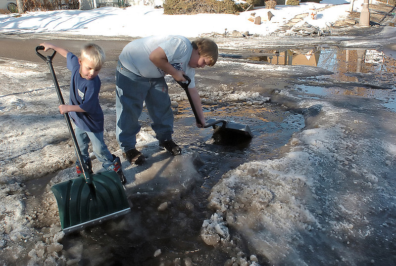 Four-year-old Shelby Peterson, left, and his brother, Oakley, 11, work together Tuesday afternoon to open a channel in a large patch of ice so that water can flow freely and not freeze up at 12th Street and Cleveland Avenue in Loveland.