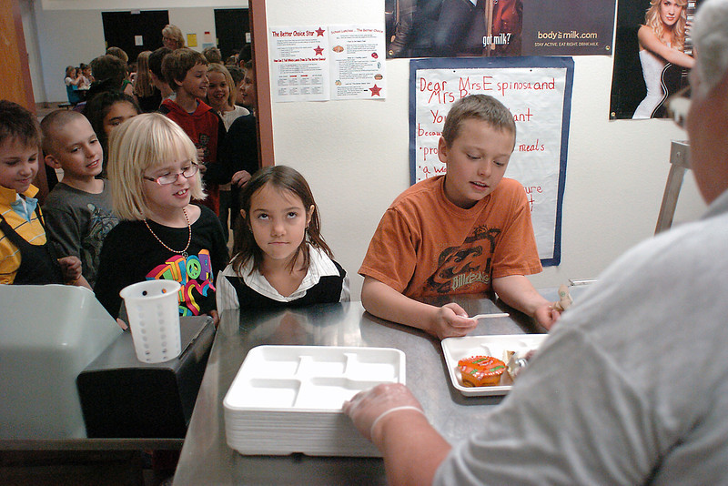 Stansberry Elementary School third graders, back from right to left, Tobin Armstrong, 9, Annabell Ballard, 9, Syd Boxley, 9, Jason Case, 9, and Josh Bush, 8, pick up their lunches from server Donna Keenan, right, who was utilizing new biodegradable trays in place of the Styrofoam ones the school used to use.