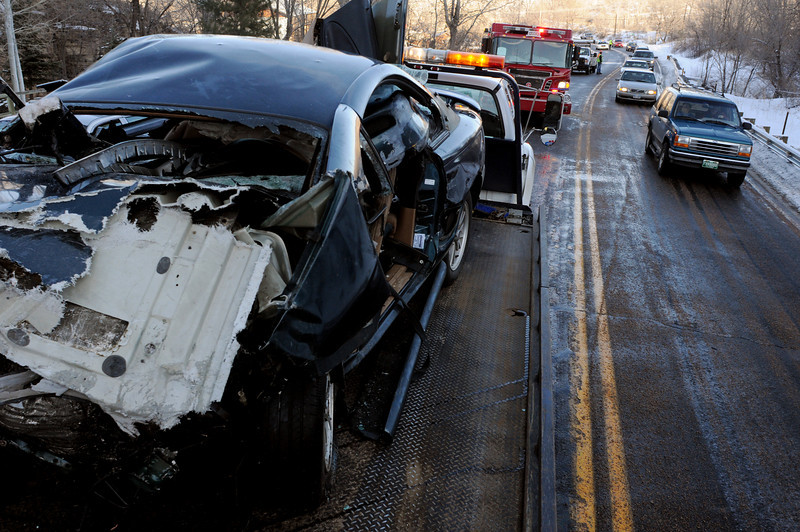 Cars move past a Mustang on a flat-bed tow truck at 9019 W. U.S. 34 where the car and a Volvo SUV collided on Monday afternoon. The Mustang was traveling eastbound on U.S. 34 from a sunny patch to a shady and icy patch of the road. The car slid and collided with the Volvo. The driver of the Mustang was extricated and taken to McKee Medical Center along with the passenger. Four people in the Volvo were also taken to McKee.