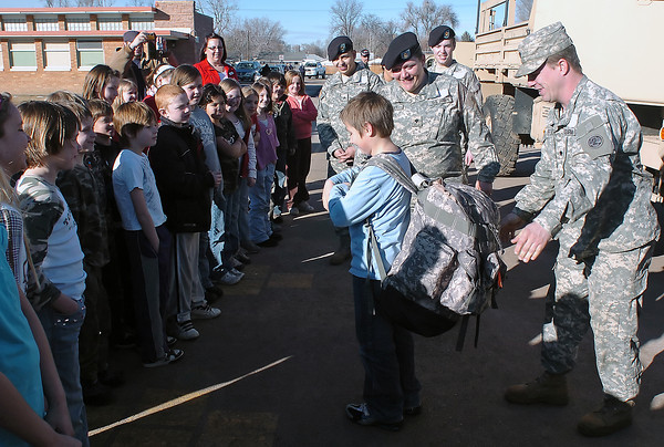 Garfield Elementary School third grader Bobby Weber, 8, center, tries on a military backpack during a visit by members of the 993 Medical Detachment out of Aurora on Friday, Jan. 29, 2010 at the school.
