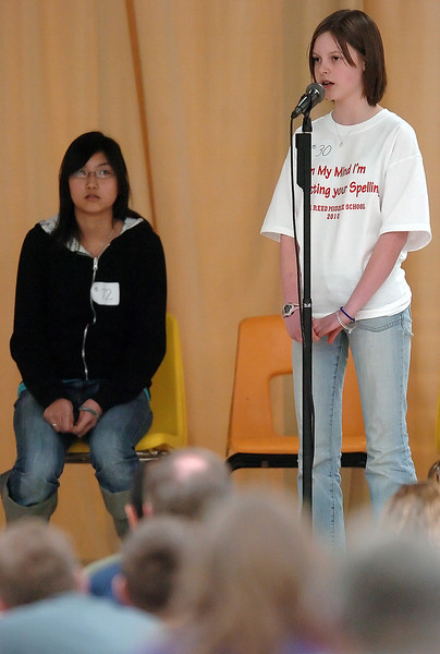 "Conrad Ball Middle School eighth grader Irena Huang, left, looks on as Bill Reed eighth grader Alexandra Ward spells a word during the final round of the Thompson School District Spelling Bee on Saturday at Walt Clark Middle School. Alexandra won the event by successfully spelling ""gynarchy"" after Irena missed ""sarsaparilla,"" to finish in second place."