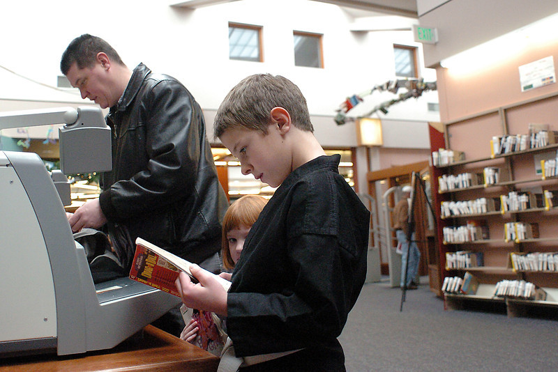 Ten-year-old Sam Foster, right, and his sister, Alana, 4, wait while their dad, Ben, uses the self-checkout machine to check out their books on Saturday at the Loveland Public Library.