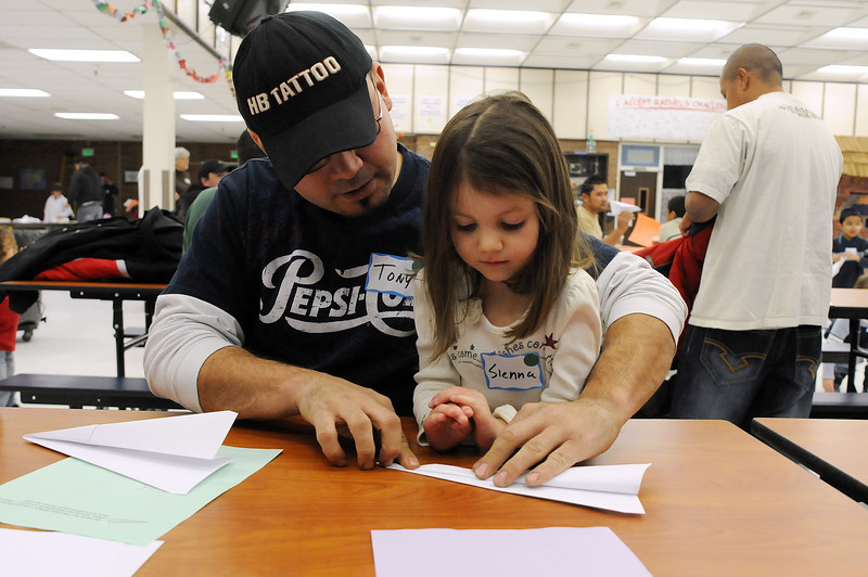 Tony Hunsinger helps his daughter Sienna, 4, to make a paper airplane during the kickoff party for We Are Awesome Dads. The WeRAD group aims to get fathers to participate more in their children's lives.