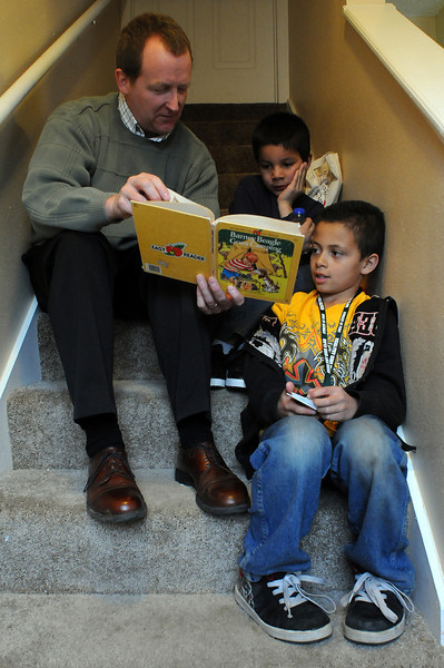 Jeff Feneis of the Loveland Housing Authority volunteers to read to Maple Terrace Kids Club members Emilio Hernandez, 7, and D'Andre Johnson on Wednesday at Maple Terrace Apartments. The club meets every Wednesday after early release to tutor and help kids stay healthy.