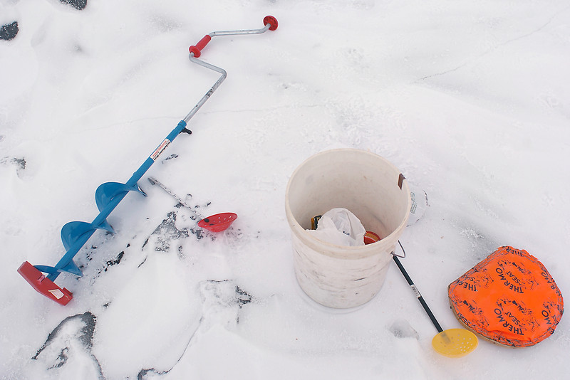 In addition to a fishing pole some additional gear used for ice fishing includes an ice auger to drill a hole, a scoop to skim ice that begins to form over the hole, various baits and lures, an insulated pad to sit on and a bucket to carry everything.
