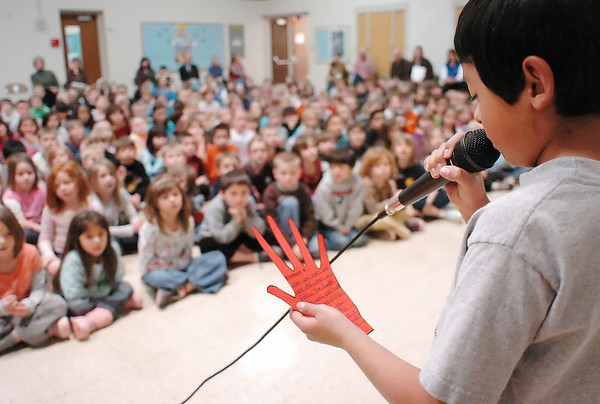 """Centennial Elementary School fifth grader Michael Gamino, 10, reads aloud during an assembly Wednesday the message he wrote on a hand of kindness as part of the Rachel's Challenge program. Students in all grades wrote positive messages on the paper hands which will be placed around the school. Michael's message was, """"When you share and care and when you follow the Eagles code you can make a difference. When you think you made a little difference, it can be big."""""""