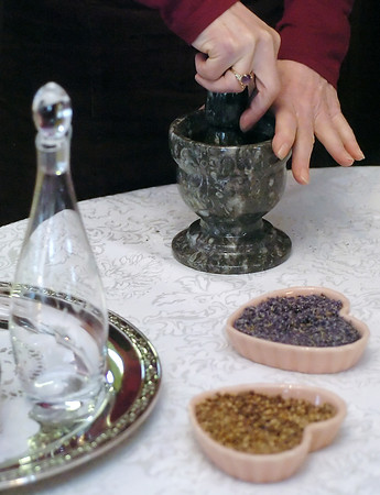Donna Wild uses a mortar and pestle to combine herbs together while making a love potion Tuesday at her Loveland home.