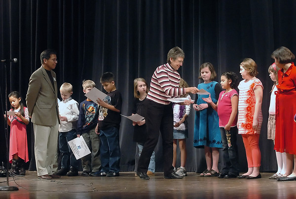 Artwork contest winners line up onstage at Thompson Valley High School's Roberta Price Auditorium Monday night as Vicki Clark, center, hands an award to Dusty Rodriguez, 9, fourth from right, whose drawing placed third for third graders at Garfield Elementary School.
