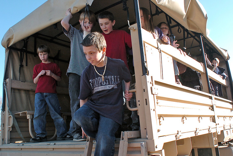 Garfield Elementary School fourth grader Braxton Bullard, 10, climbs down from a U.S. Army Light Mobile Tactical Vehicle while checking it out with classmates Friday at the school. Back from left are Connor Leichliter, 9, Kether Taylor, 10, and Walker Grove, 9.