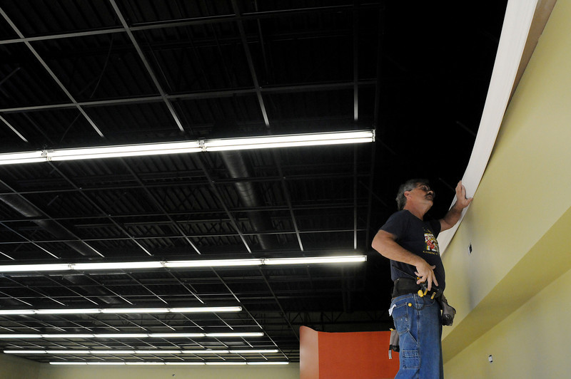 Trim carpenter Dean Dushack installs crown moulding at the new Sherwin-Williams paint store at 2033 West Eisenhower on Thursday.