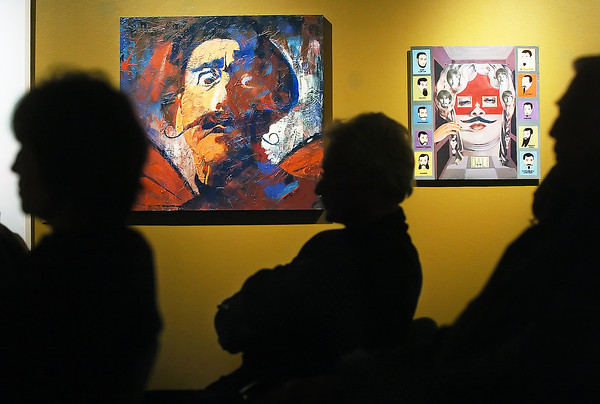 "Attendees to a presentation called ""Dali and Me!"" are silhouetted in front of several paintings on Saturday in the Foote Gallery at the Loveland Museum/Gallery.  At rear left is ""Monarchy,"" by Mollie Walker Freeman and at right is a collage on wood called ""'A Hard Man is Good to Find' -Mae West,"" by Zoa Ace. The exhibit called ""Twirling Dali's Moustache"" runs through Feb. 14 and features a variety of pieces inspired by the works of artist Salvador Dali."