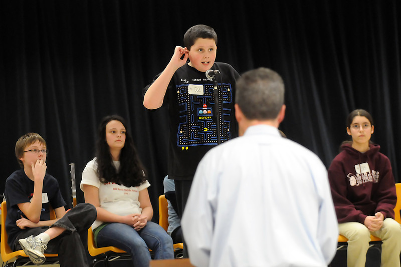 William Dolan, 11, center, stands at the microphone onstage at Walt Clark Middle School as pronouncer Steve Hanna looks on during a round of the Thompson School District Spelling Bee on Saturday. Dolan will be an alternate and the top six finishers earned the privilege to compete at the Denver Post Colorado State Spelling Bee in March.  Seated at rear from left are Ken Kubik, 13, who finished in second place, champion speller Rocky Eisentraut, 13, and third place finisher Olivia Conde.