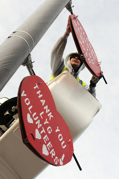 Jerry Hatten hangs heart-shaped signs on a light pole along W. Eisenhower Boulevard while volunteering with other City of Loveland employees to decorate the roadway Saturday morning.