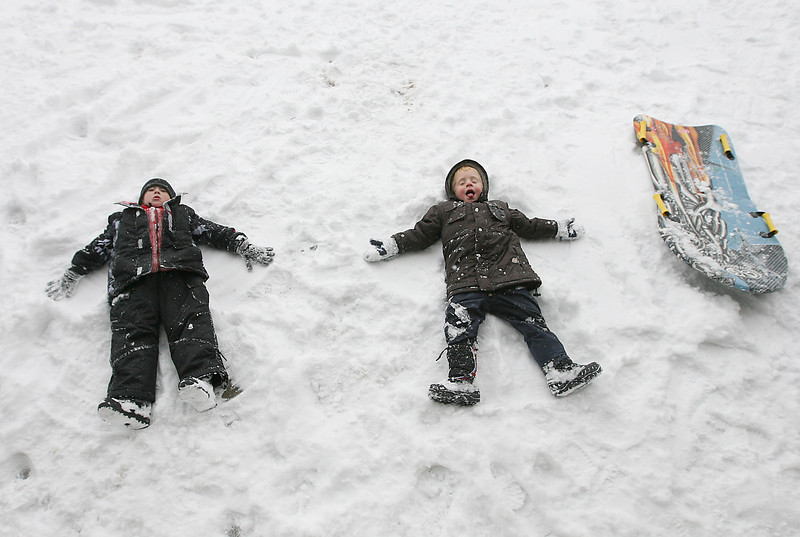 Ian Christensen, 6, left and Nathan Temple, 3, make snow angels in the snow Sunday at North Lake Park near the Norma & Lynn Hammond Amphitheater. The two boys made friends while playing in the snow. Photo by Gabriel Christus