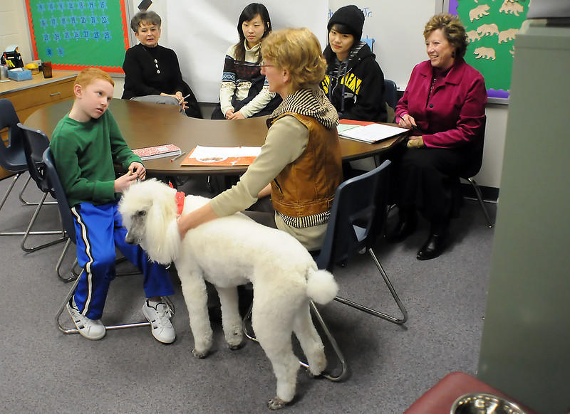 Nine-year-old Ben Norton, left, chats with Kathy O'Loughlen last Tuesday at Garfield Elementary during a visit to the school with a standard poodle named Barley for the Human Animal Bond in Colorado program. At rear from left are HABIC co-founder Georgia Granger, Gu Ye Sul and Si-nae Cheon from Kong-Ju National University in Korea and counselor Sandy Cox.