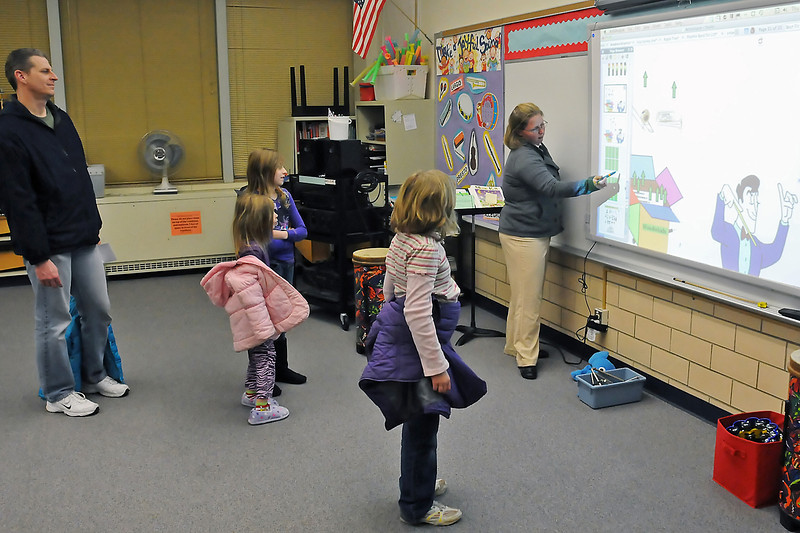 Garfield Elementary School music teacher Courtney Wooden, right, demonstrates an interactive music instruction program Thursday evening during an open house event at the school. From left are Bryan Cotton, Leanne Cotton, 4, Kirsten Cotton, 9, and Michaela Rood, 9.
