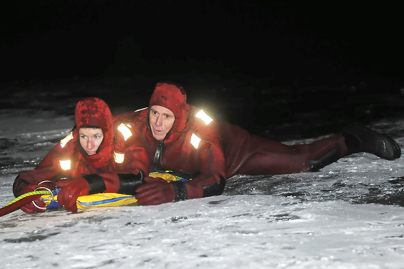 Loveland Fire and Rescue Department fire inspection technician Sandra Friedrichsen, left, and firefighter Randy Kolb practice ice rescue techniques Wednesday evening near an open area of water on the north side of Lake Loveland.