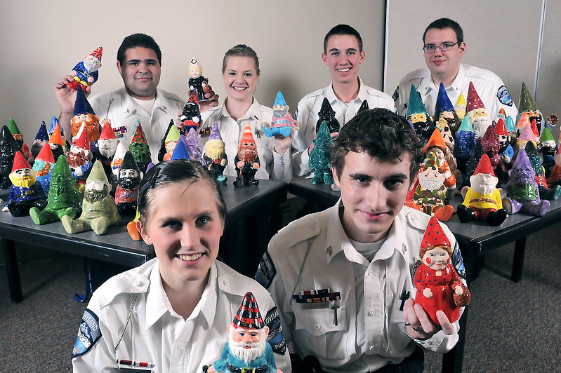 Members of the Loveland Police Department Explorers pose Friday at the station with ceramic gnomes that they and other department employees decorated to use in a fundraiser for the Explorers. At front are Hunter Redding, left and Gavin Buford and at rear from left are Armando Trujillo, Nicole Foote, Matt Oreskey and Donald Blake.