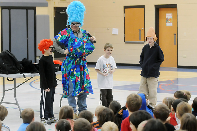 "Storyteller and author Gary Hogg, center, dressed as ""Beautiful Beuhla,"" gets some help from New Vision Charter School students while conducting a program called Writing is Exciting! on Tuesday afternoon in the gymnasium. Back from left are Jackson Dexter, 7, Hogg, Isaac Chase, 7, and Jaromy Morgan, 7."