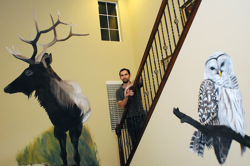 Fort Collins resident Brett Rosenberg poses in front of two custom murals he's painted on the walls of his home.