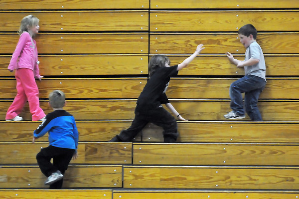 Youngsters play a game of freeze tag in the bleachers at Loveland High School during a wrestling meet Thursda evening against Poudre. From left are JoLee Huffaker, 5, Matthew Stalnaker, 6, Strider Corley, 8, and Caleb Wertz, 9.