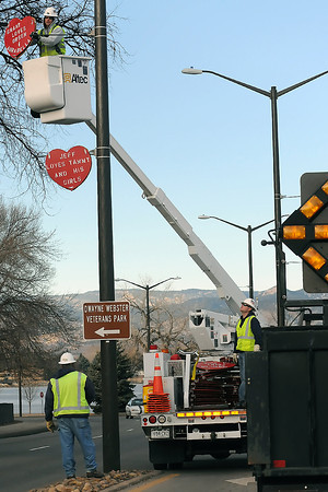 City of Loveland employees volunteer their time to hang signs with Valentines Day messages along W. Eisenhower Boulevard on Saturday morning. At top is Jerry Hatten and bottom from left are Paul Polston and Andrew Stewart.