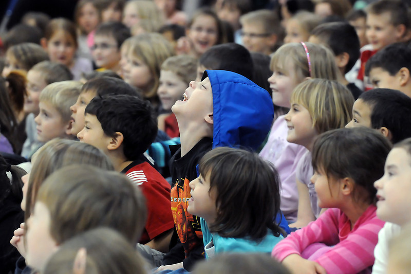 "New Vision Charter School kindergartner Tavin Adamson, 6, center, laughs along with his classmates as guest speaker Gary Hogg tells a story during an assembly in the gymnasium Tuesday afternoon. Hogg is storyteller and author of children's books from Huntsville, Utah who was at the school to give the students writing tips through his program called ""Writing is Exciting!"""