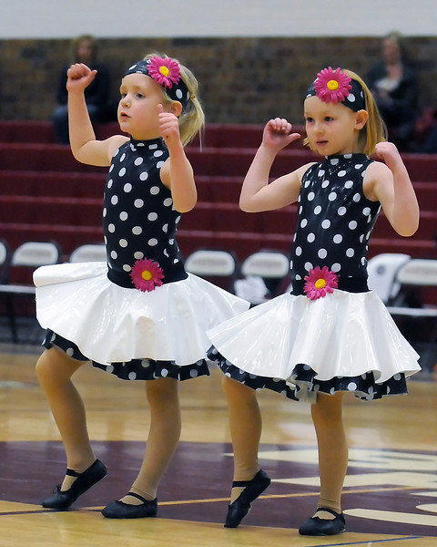 Berthoud residents Aubrey Sundberg, 5, left, and Anya Knoll, 6, dance together Saturday night in the gymnasium at Berthoud High School during halftime of the boys basketball game against Niwot. The girls take dance lessons together at Just For Kix.