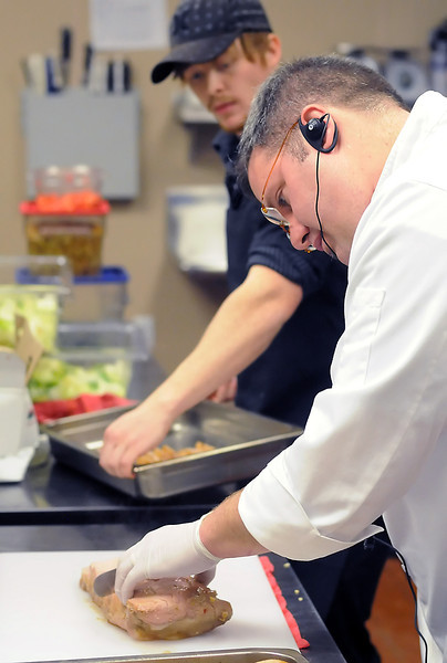 Midtown Events owner/chef Chris Walters, right, slices some Asian marinated pork loin while cook Stewart Klair looks on in the kitchen at the Midtown Arts Center located at 3750 S. Mason St. in Fort Collins.