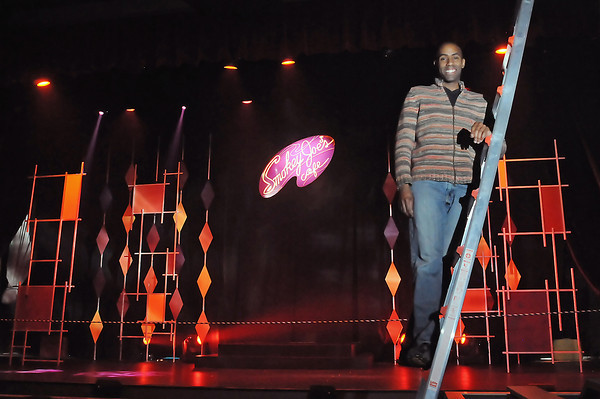 """Kenneth Moten, artistic director for the Dinner Theatre at the Midtown Arts Center, poses Wednesday in front of the stage for the just opened production of """"Smokey Joe's Cafe."""""""