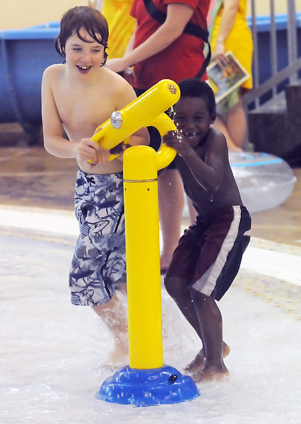 Jakob Haehre, 9, left, and his brother, Moise Haehre, 5, share a laugh while trying to squirt each other with a water gun at the Chilson Recreation Center's pool during a recent family outing.