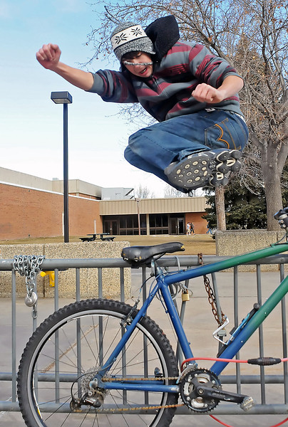 Wesley Edmunds, 15, leaps over a bicycle rack while practicing parkour moves Saturday afternoon outside Thompson Valley High School. Parkour is an activity where the participant uses their body to overcome obstacles in urban areas by running and jumping.