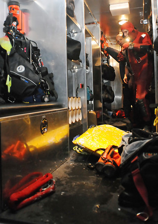 Loveland Fire and Rescue Department Lt. Robert Carmosino, back, and firefighter Randy Kolb change out of drysuits in the back of the department's dive rescue truck after a training session in ice rescue techniques Wednesday evening on the north side of Lake Loveland.