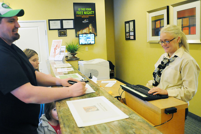 Members of the Bryan family, from left, Greg, Kelsie, 10, and Lexi, 4, are assisted by Jackie Heavener at the reception desk of La Quinta Inn & Suites, 1450 Cascade Ave. as they register for a room Saturday.
