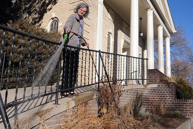 First Church of Christ, Scientist church member Joyce Dempsey waters plants outside the entrance to the church at Garfield Avenue and Fourth Street in downtown Loveland on Friday afternoon.