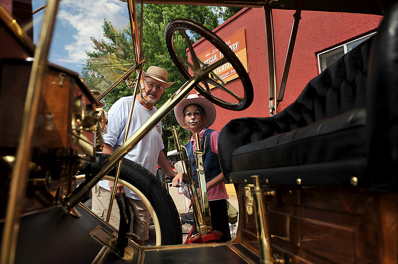 Arland Washburn and Kenna Washburn, 10, survey a 1907 Darracq Saturday at the Classic Car Show during Summerfest in Loveland. Both Washburns, who are from Loveland, said they enjoyed the event, Kenna liked the face painting in particular.